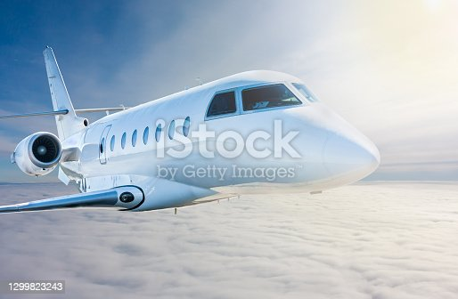 White modern luxury private jet flies in the air above the clouds. Close-up view business airplane