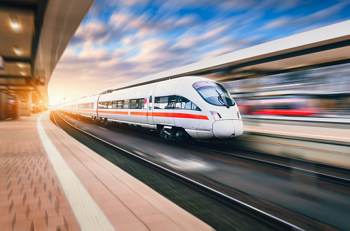 White modern speed train in motion on railway station at sunset. Train on railroad track with motion blur effect in Europe in evening. Railway platform. Industrial landscape. Railway tourism