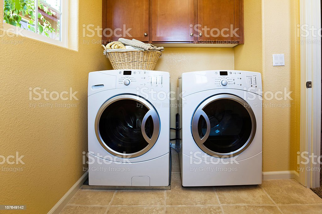 White modern washer and dryer in home's laundry room. stock photo