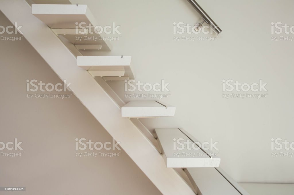 white modern wooden Staircase and white wall close-up, house interior
