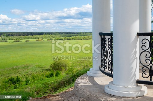 White monument with columns on a hill against fields and blue sky.