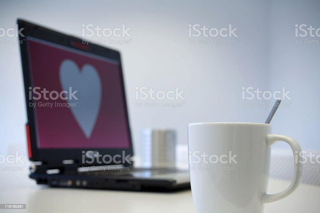 white mug and heart shape on a notebook stock photo