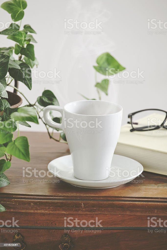 White mug and saucer with book on wooden table royalty-free stock photo