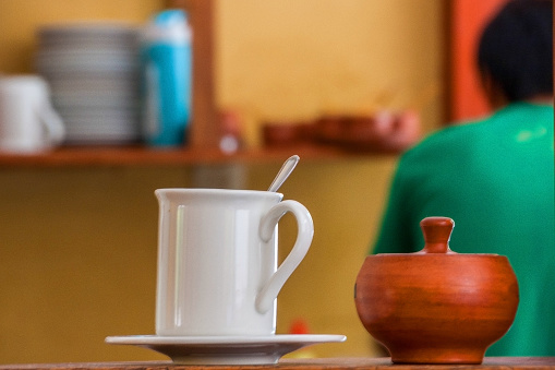 White mug and wooden sugar-bowl at table on cafe background