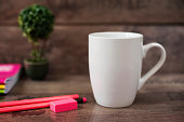 White mug mockup. Blank mug. Coffee mug mockup with bright neon colors pencils and notebooks. Potted plant bonsai behind. Rustic wooden background.