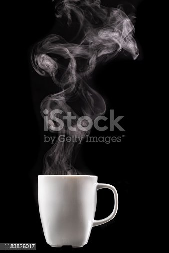 A white mug of warm drink and steam. Tasty hot coffee on a dark table. Black background.