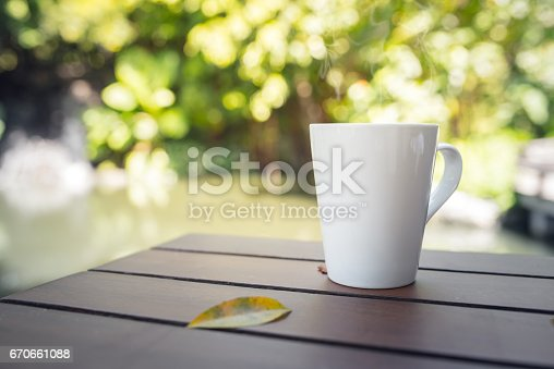 istock white mug on a wooden table in the garden. 670661088