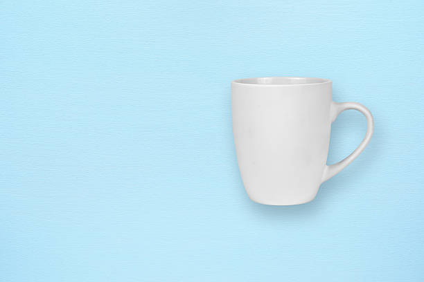 White mug on blue background stock photo