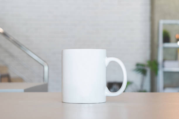 White mug on table and modern room background. Blank drink cup for your design. Can put text, image, and logo. stock photo