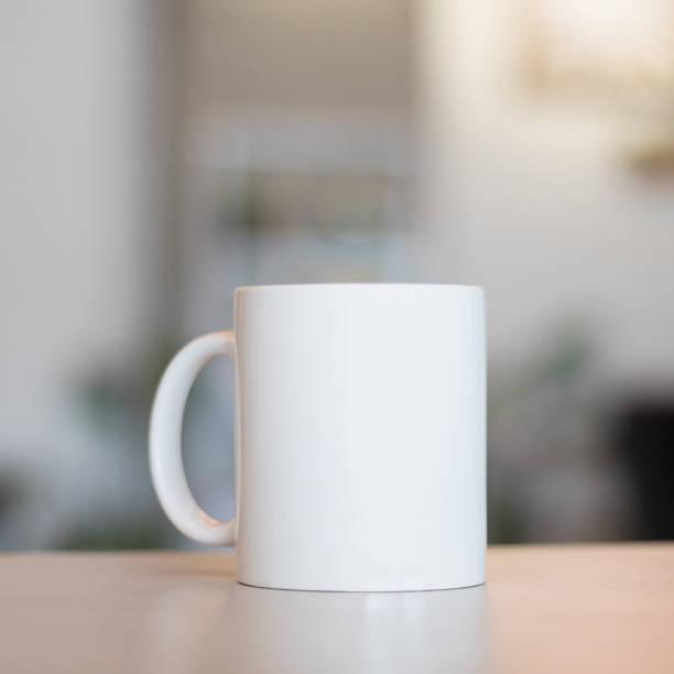 blanco taza sobre la mesa y el fondo de la habitación moderna. taza de la bebida en blanco para su diseño. puede poner texto, imagen y logotipo. - taza fotografías e imágenes de stock