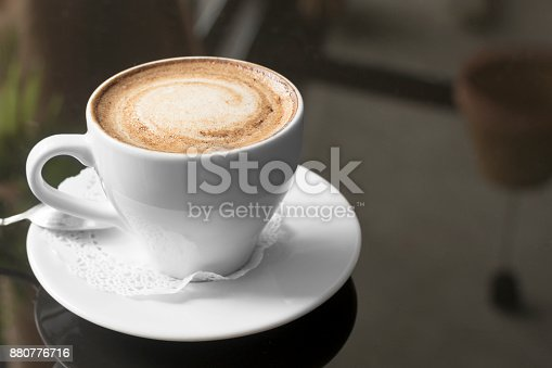 istock White mug with coffee. A fragrant cappuccino. An unusual tinted photograph with a bokeh. 880776716