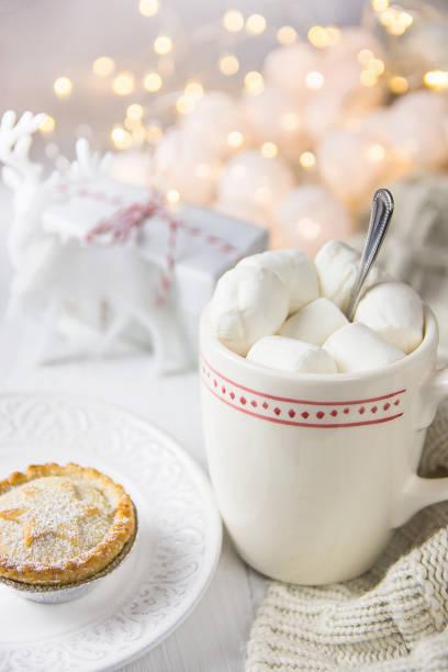 weiße tasse mit heißer schokolade kakao trinken und marshmallows am oberen mince pie auf platte. garland lichterglanz gestrickte pullover geschenk box weihnachten neujahr advent morgen gemütlich - strickmantel stock-fotos und bilder