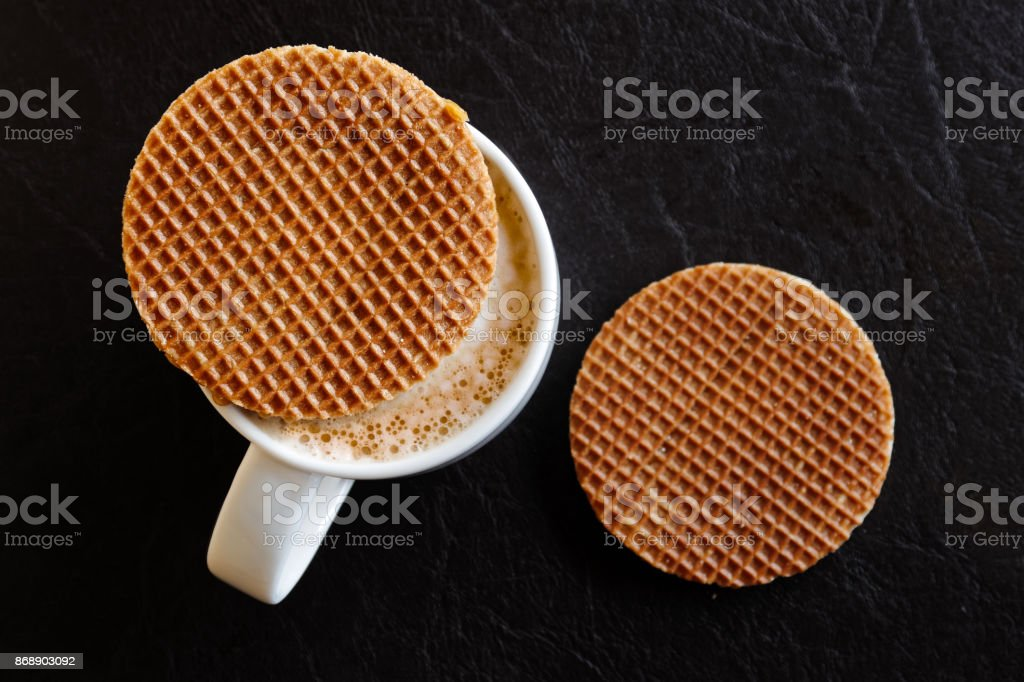 White mug with milky frothy coffee and a round waffle biscuit on top next to another waffle biscuit isolated on black leather from above. – zdjęcie