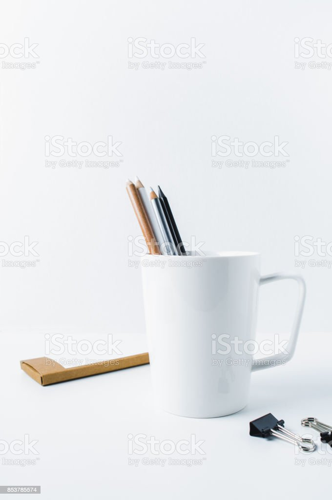 White mug with pencils and office supplies on white background stock photo