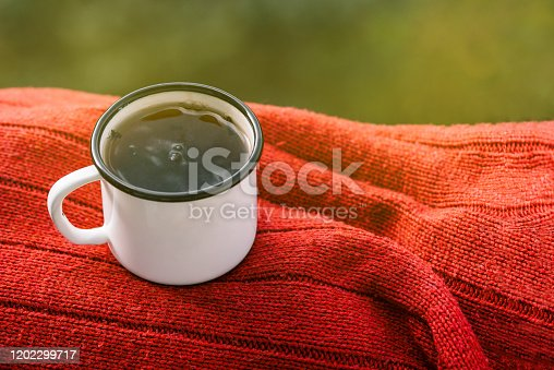 istock White mug with tea on a red sweater. Metal mug on the nature in the summer or spring. Morning breakfast. The concept of the approaching summer of romance and love. Cozy atmosphere. 1202299717