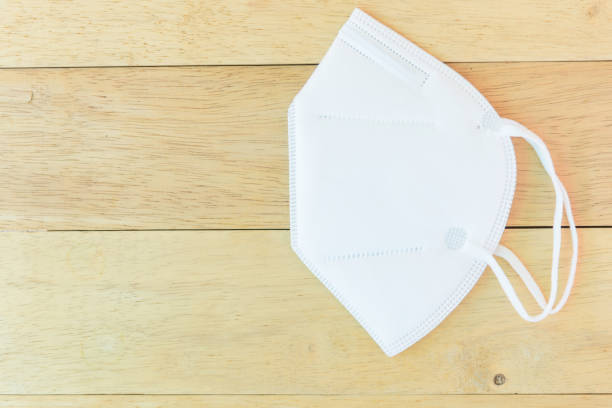 White N95 Mask on wood plate stock photo