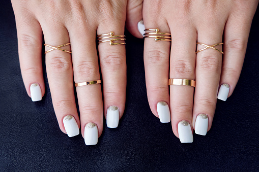 istock White nail art manicure, hands with fashion gold rings 594955208