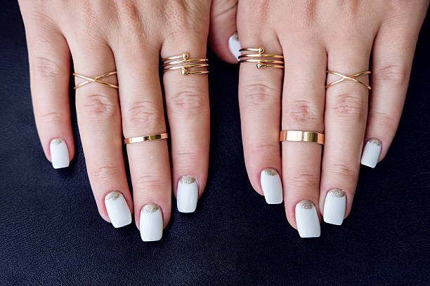 white nail art manicure, hands with fashion gold rings - bague bijou photos et images de collection