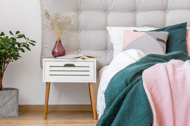 White nightstand in pastel bedroom stock photo