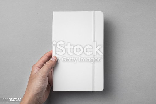 Design concept - top view of close white notebook hold by mans hand on grey background for mockup. real photo, not 3D render