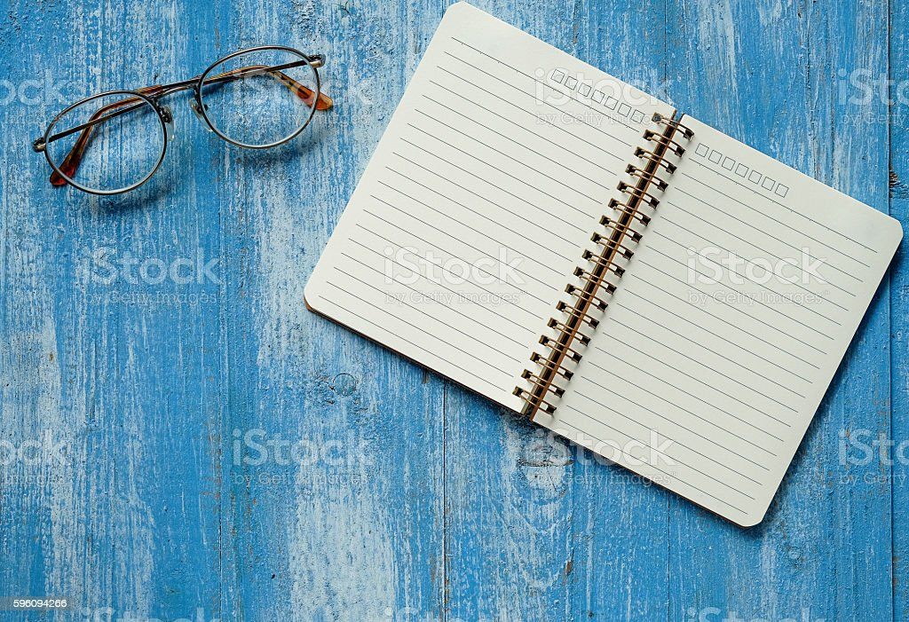White notebook with glasses on blue wooden floor. royalty-free stock photo