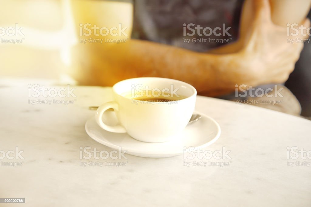 white of hot ceramic coffee cup on table with blur arm of adult man background stock photo