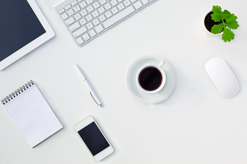 istock White Office Desk Table Electronic Gadgets Stationery Coffee Cup Flower 499691622