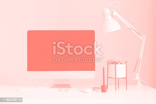White office desk table with computer keyboard, mouse, monitor, graphic tablet, smartphone, succulent plant and other office supplies in trendy coral color. Top view, copy space, flat lay