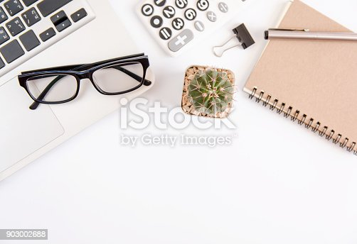 604021340 istock photo White office desk table, workspace office with laptop, smartphone black screen,pen,calculator, glasses, Top view with copy space 903002688