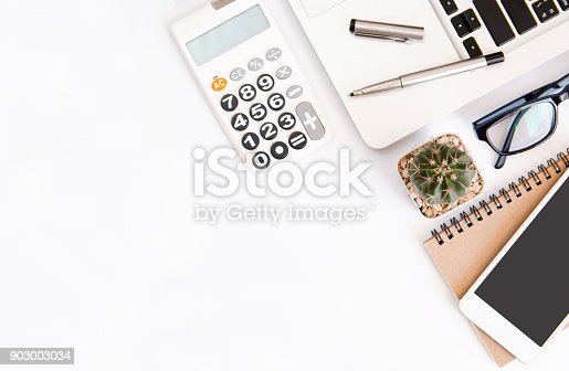 604021340 istock photo White office desk table, workspace office with laptop, smartphone black screen,pen,calculator, glasses, Top view with copy space 903003034