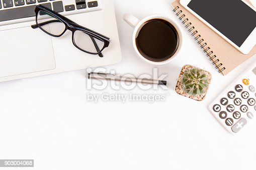 604021340 istock photo White office desk table, workspace office with laptop, smartphone black screen,pen,calculator, glasses, Top view with copy space 903004068