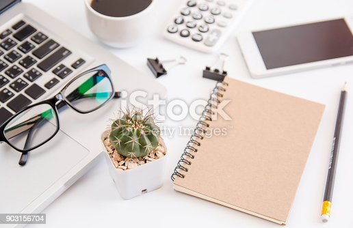 604021340 istock photo White office desk table, workspace office with laptop, smartphone black screen,pen,calculator, glasses, Top view with copy space 903156704