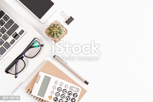 604021340 istock photo White office desk table, workspace office with laptop, smartphone black screen,pen,calculator, glasses, Top view with copy space 903156740