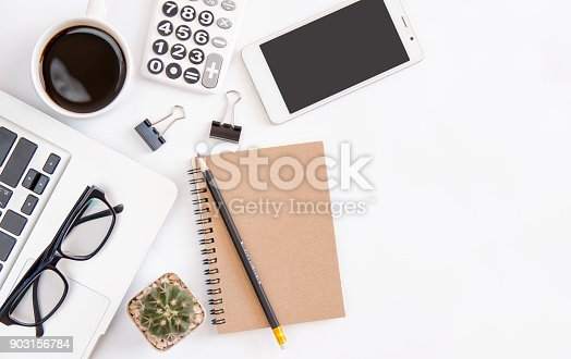 604021340 istock photo White office desk table, workspace office with laptop, smartphone black screen,pen,calculator, glasses, Top view with copy space 903156784
