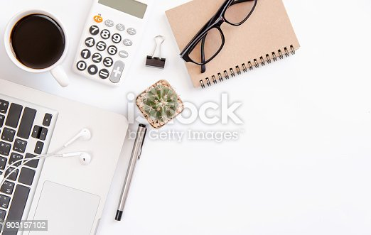 604021340 istock photo White office desk table, workspace office with laptop, smartphone black screen,pen,calculator, glasses, Top view with copy space 903157102