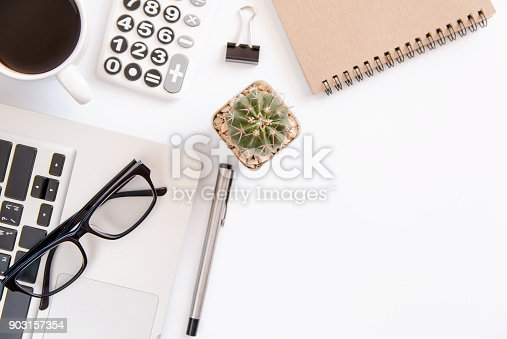 604021340 istock photo White office desk table, workspace office with laptop, smartphone black screen,pen,calculator, glasses, Top view with copy space 903157354