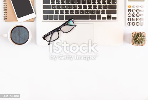 604021340 istock photo White office desk table, workspace office with laptop, smartphone black screen,pen,calculator, glasses, Top view with copy space 903157430