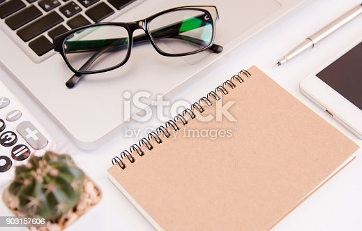 604021340 istock photo White office desk table, workspace office with laptop, smartphone black screen,pen,calculator, glasses, Top view with copy space 903157606