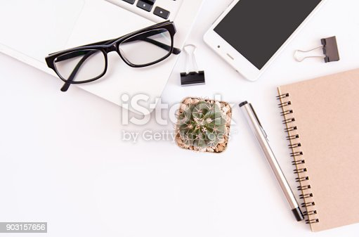 604021340 istock photo White office desk table, workspace office with laptop, smartphone black screen,pen,calculator, glasses, Top view with copy space 903157656