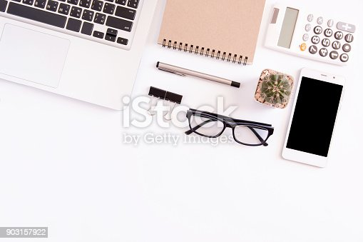 604021340 istock photo White office desk table, workspace office with laptop, smartphone black screen,pen,calculator, glasses, Top view with copy space 903157922
