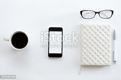 615494694 istock photo White office desk with glasses, mobile phone, coffee and pen 615494448