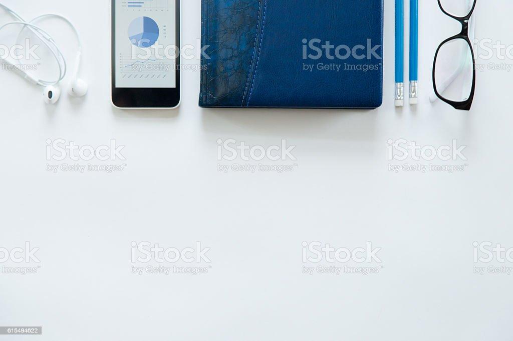 White office desk with glasses, mobile phone, earphones stock photo