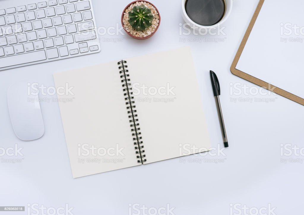 White office desk with notebook, pen, cactus, cup of coffee, mouse, computer. Top view and copy space for mockup, website banner, background, presentation and marketing material. stock photo