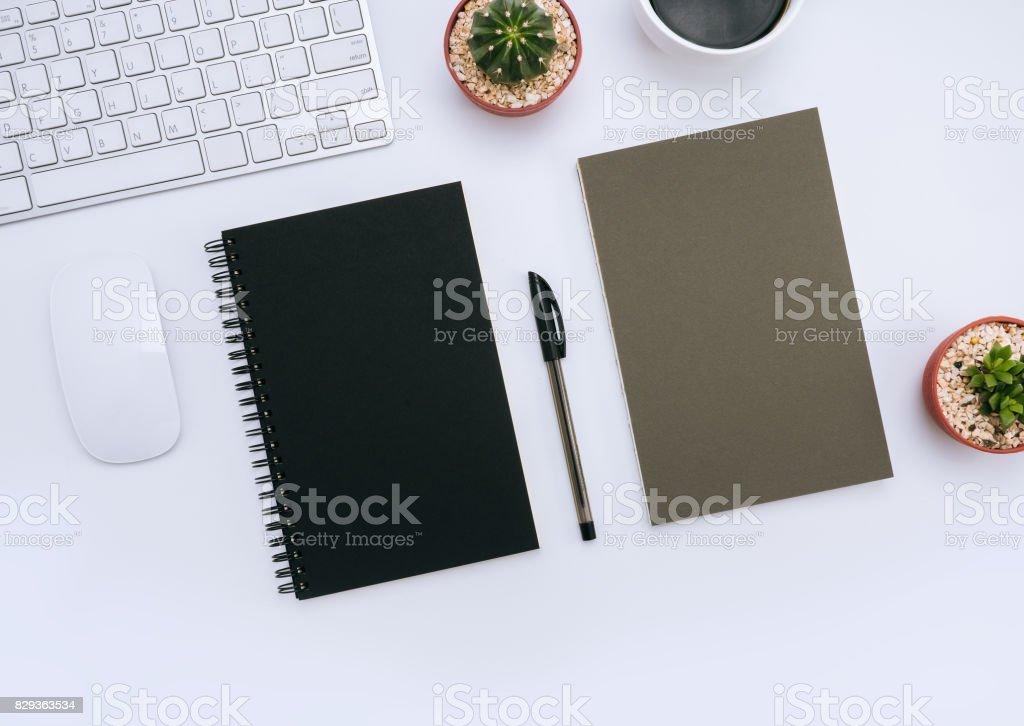 Photo de stock de bureau blanc avec blocnotes stylo petite plante