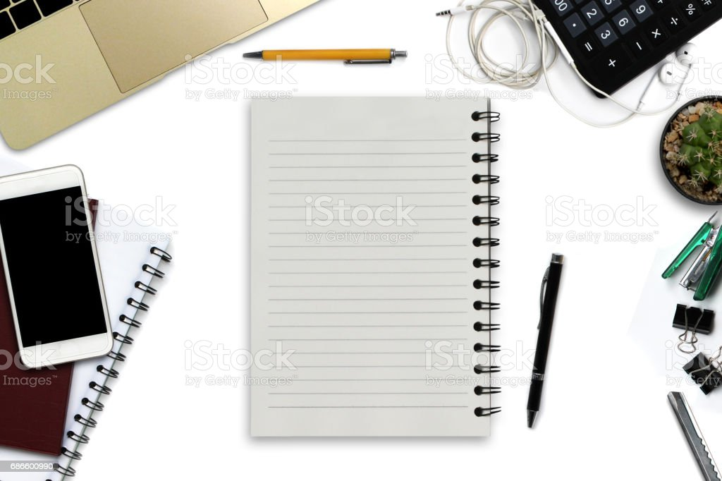 White office desk with smartphone with black screen, pen, laptop computer, notepad with copy space, and supplies. Top view with copy space royalty-free stock photo