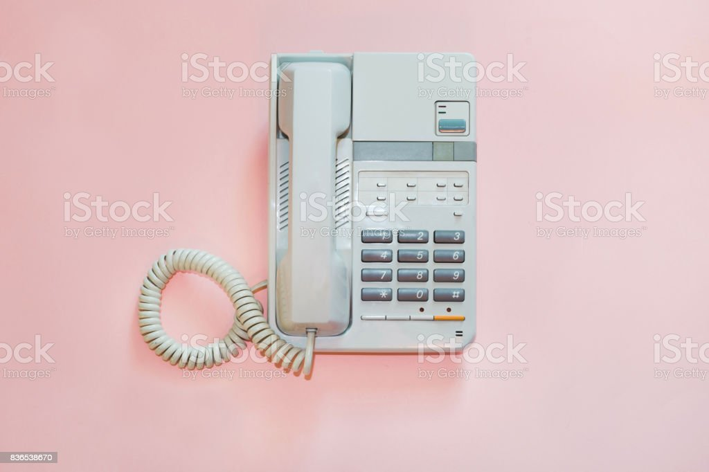 White office telephone on pink background. stock photo