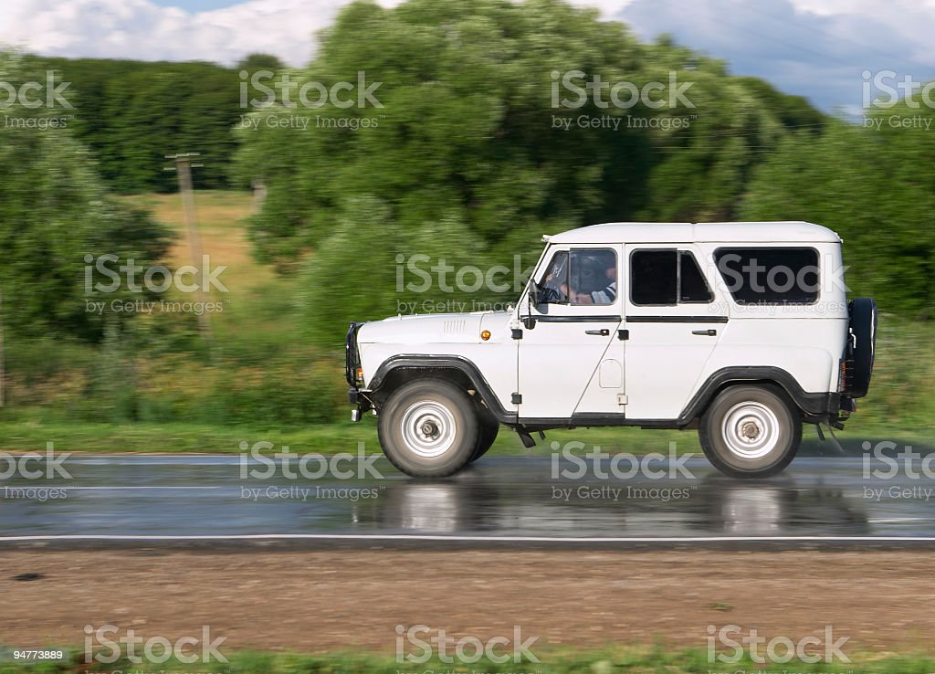 White off-road car driving along a wet road stock photo
