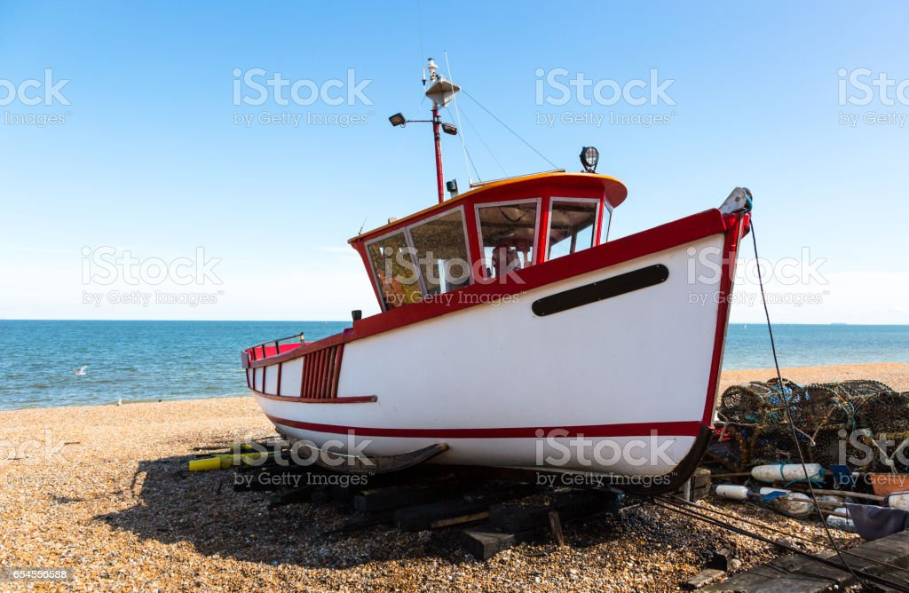 White old fishboat with red edges on beach stock photo