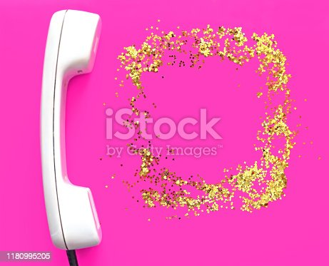 White old handset on fuchsia background. Place for text. Glitter golden stars as a frame. Holiday concept. New Year and Christmas holiday