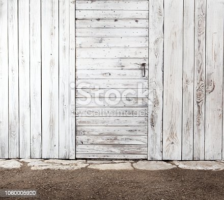 white old shabby wooden door in aged wooden wall, exterior of tool shed for vegetable garden, copy space blank template background